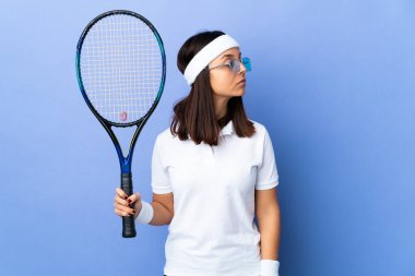 Young woman tennis player over isolated background keeping the arms crossed