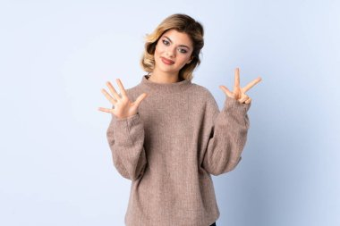 Young Russian woman isolated on blue background counting eight with fingers