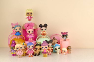 Many colorful plastic LOL dolls on table. LOL Surprise series toys manufactured by MGA Entertainment inc.