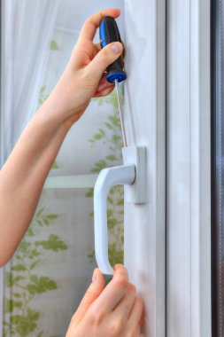 Close-up of hand with screwdriver is dismantling plastic window.