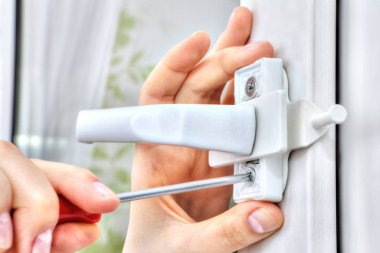 Hand with screwdriver tightens fixing screw of window  restricto