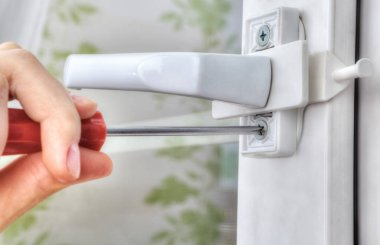 Close-up of hand with screwdriver, tighten the screw stopper win