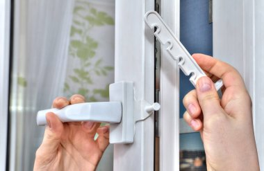 Mounting opening restrictor for PVC window, close-up.