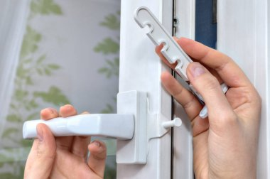Installation of opening limiter on the pvc window, close-up.