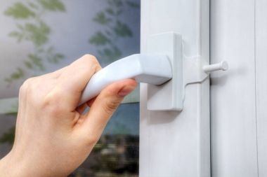 Hands turning handle of plastic window on which opening delimite