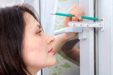 She outlines the stopper attachment points on PVC windows.