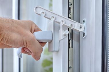 Men's hand opens a plastic window with stop turning.