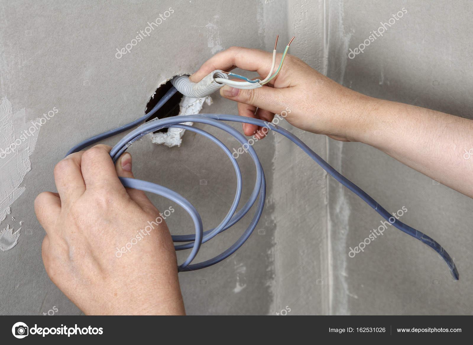 Wand Loch Kabel durchziehen, Hände Elektriker Nahaufnahme ...