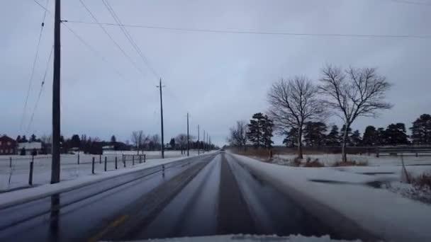 Jízda na venkově Road v zimě se sněhem na kraji silnice v den. Driver point of View Pov Driving Street s sněhem na stromech s oblačnou oblohou.