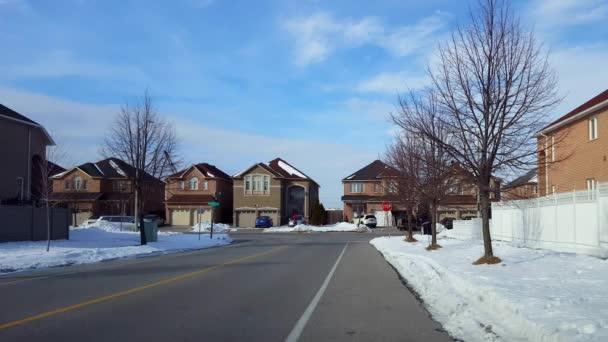 Autos fahren, Menschen laufen und Flugzeuge fliegen über Wohnhäuser in Vorstädten. Stoppende und fahrende Fahrzeuge auf der Straße an der Kreuzung mit City-Stoppschildern, Menschen gehen auf dem Gehweg, im Winter fliegen Flugzeuge drüber.