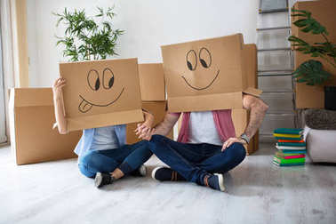 Funny happy couple sitting on floor wearing cardboard boxes