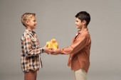 two happy brothers holding yellow gift box while looking at each other isolated on grey