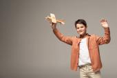 usmívající se chlapec drží dřevěnou hračku letadlo a mává rukou na kameru izolované na šedé