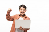 cheerful boy holding laptop and showing winner gesture isolated on white