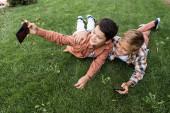 veselý chlapec brát selfie na smartphone zatímco ležel na trávě s bratrem