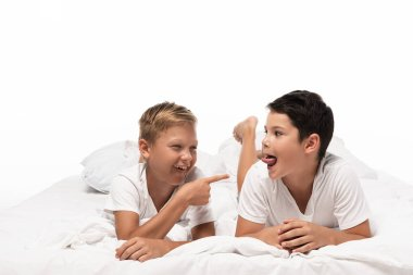 cheerful boy pointing with finger at brother sticking out tongue isolated on white