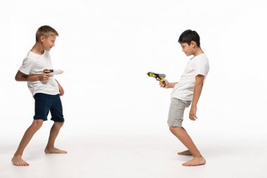 two brothers aiming at each other with toy guns on white background