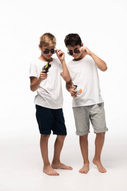 Two brothers in sunglasses holding toy guns and looking at camera while playing gangsters isolated on white stock vector
