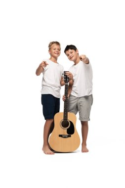 two cheerful brothers pointing with fingers at camera while standing with acoustic guitar on white background