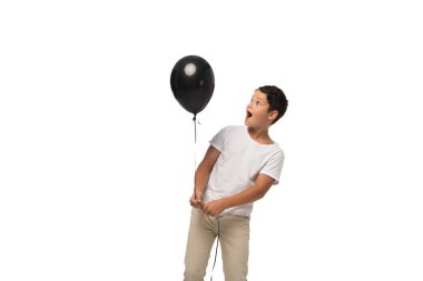 Surprised boy looking at black balloon while standing isolated on white stock vector