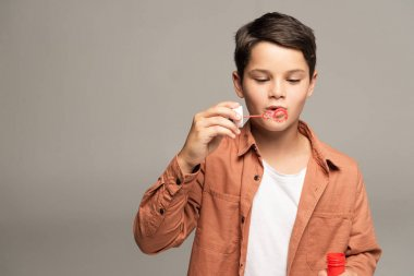 cute boy blowing soap bubbles isolated on grey