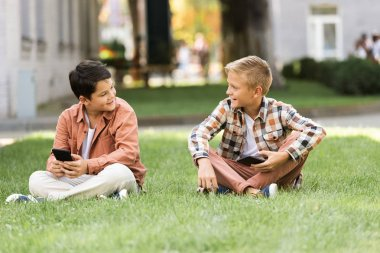 two smiling brothers talking while sitting on lawn with smartphones