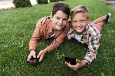 two happy brothers lying on grass, holding smartphones and looking at camera