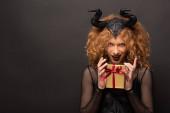 Fotografie sexy Frau im bösartigen Kostüm mit Geschenkschachtel für Halloween auf schwarz
