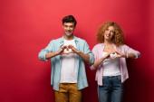 krásný šťastný pár se srdečními příznaky, izolované na červené