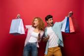 šokovaný pár při pohledu na nákupní tašky, izolované na červené