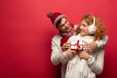 glückliches Paar im Winteroutfit mit Weihnachtsgeschenk auf Rot