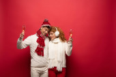 beautiful couple in winter outfit hugging and holding champagne glasses, on red