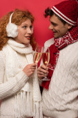 schöner Mann und Frau im winterlichen Outfit mit Champagnergläsern, isoliert auf Rot