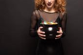 Fotografie abgeschnittene Ansicht einer Frau, die Topf mit Bonbons für Halloween auf Schwarz hält