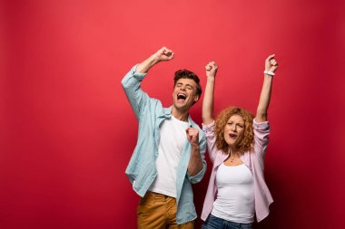 excited young couple celebrating triumph, isolated on red