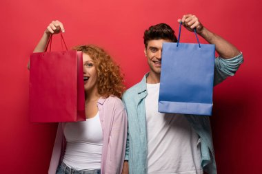 Güzel, gülümseyen bir çift ellerinde alışveriş torbaları, kırmızıda izole edilmiş.