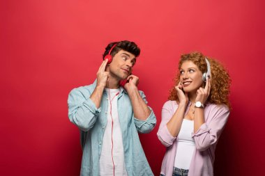 beautiful happy couple listening music with headphones and looking at each other, isolated on red