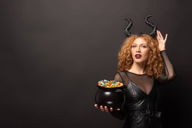 curly redhead woman in maleficent costume holding pot with candies for halloween on black