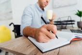 Válogatott fókusz a kerekesszékes férfi tartó csésze és írás notebook íróasztal