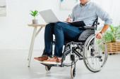 Ausgeschnittene Ansicht eines Mannes im Rollstuhl, der in Notizbuch und Laptop schreibt
