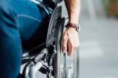 Ausgeschnittene Sicht auf Mann, der Hand an Rollstuhl hält