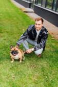 Férfi póráz petting francia bulldog a gyepen, és mosolyog a kamera