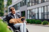 Fotografie Lächelnder behinderter Mann mit französischer Bulldogge auf der Stadtstraße