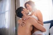attraktive Freundin in Unterwäsche küsst und umarmt mit Freund