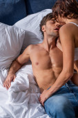 back view of girlfriend kissing and hugging shirtless boyfriend in bed