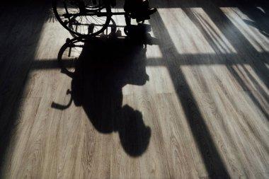 Silhouette on floor of man sitting on wheelchair stock vector