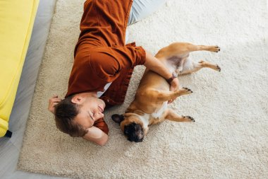 Overhead view of man with with french bulldog lying on carpet