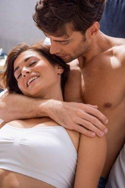 Boyfriend hugging smiling girlfriend in underwear with closed eyes stock vector