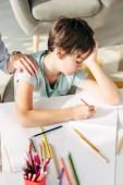 oříznutý pohled dětského psychologa dotýkajícího se smutného dítěte s dyslexií