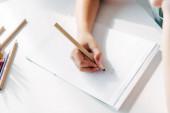 ořezaný pohled na dítě s dyslexií kreslení na papíře s tužkou